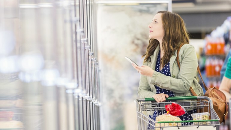 Woman in grocery store using phone